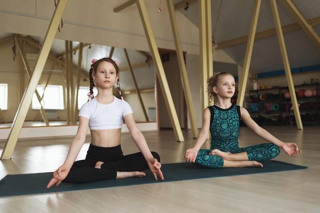 ヨガを練習している小さな女の子は、スタジオの蓮華座に座って瞑想に従事しています