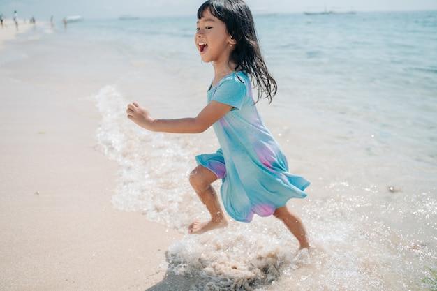 小さな女の子が走ってビーチで笑う