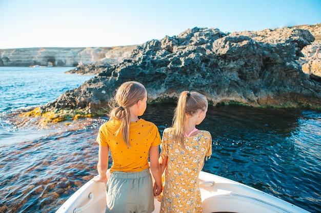 Маленькие девочки, плывущие на лодке в чистом открытом море