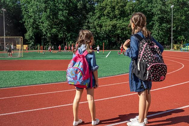 Девочки-школьники с рюкзаками на стадионе смотрят, как мальчики играют в футбол.
