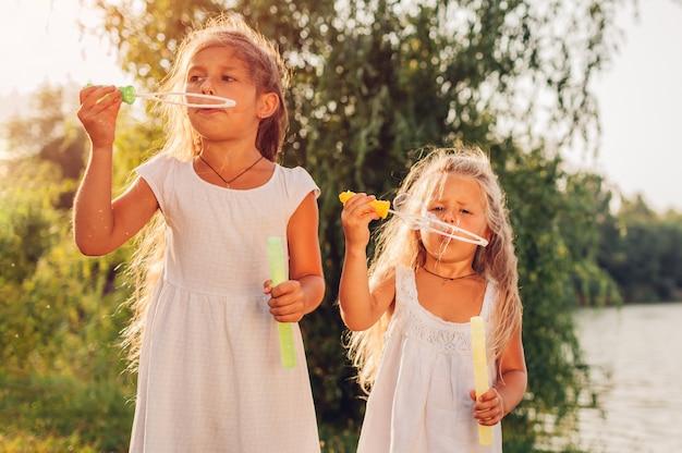春の公園でシャボン玉を吹く女の子の姉妹。屋外で楽しんでいる子供たち。