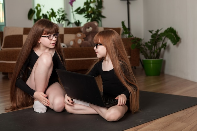 小さな女の子の姉妹は自宅でオンラインレッスンの体操を開催します