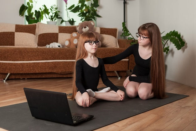 Little girls sisters hold an online lesson gymnastics at home