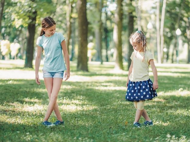 夏の外の緑豊かな公園で一緒にバレエトレーニングをしている小さな女の子の姉妹