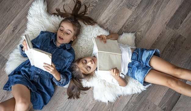 Little girls sisters read books lying on the floor, top view.