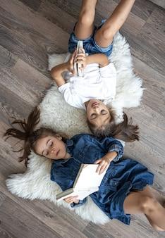 Сестры маленькие девочки читают книги, лежа на полу, вид сверху.