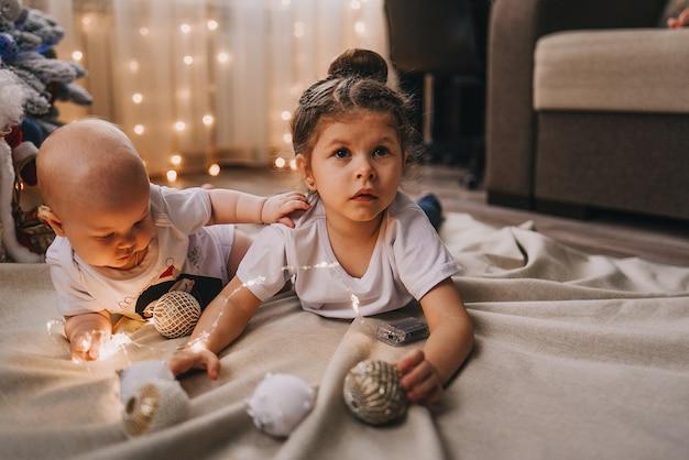 クリスマスツリーの下に座っている小さな女の子