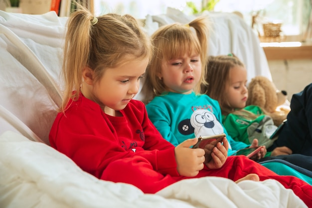 Little girls in soft warm pajamas playing at home