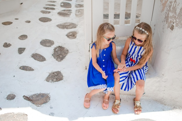 Little girls at street of typical greek traditional village in greece