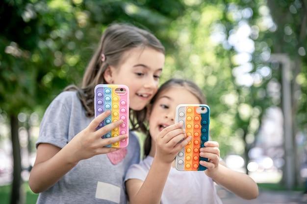小さな女の子は、流行のケースで電話を使用して、ストレスを解消します。