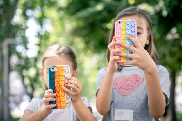 Little girls use phones in trendy cases for anti stress pop it.