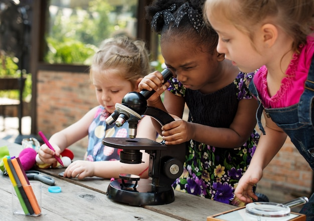Little girls using microscope learning science class