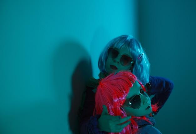화려한 가발과 하트 모양의 선글라스를 쓴 어린 소녀들이 디스코 조명 배경에서 사진 촬영을 위해 포즈를 취했습니다.