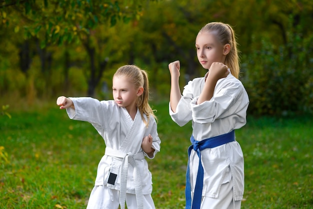 Little girls in white kimono during training karate exercises at summer outdoors