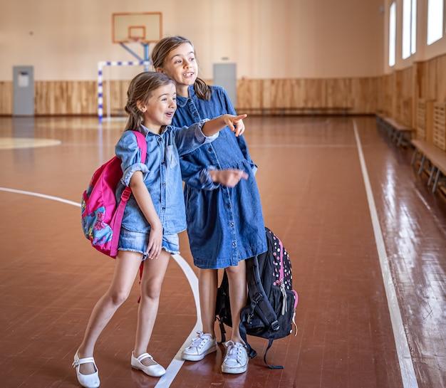 空の学校の体育館でバックパックを持った少女。