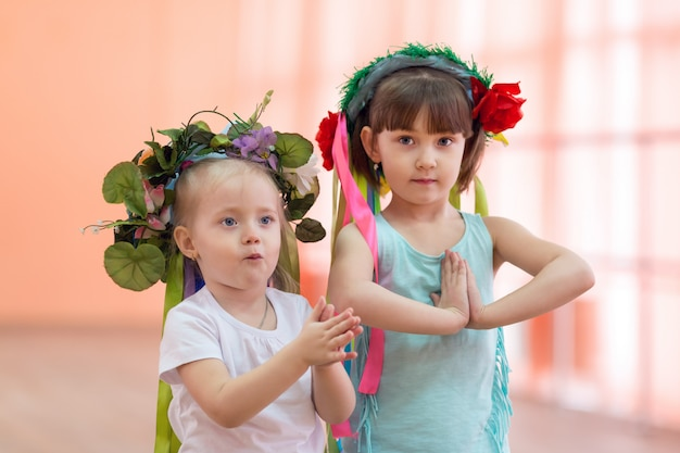 Little girls with flowers on their heads.