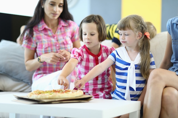 Little girls with mothers sit on couch and take slices of pizza