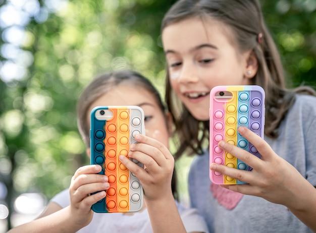 여드름이 있는 케이스에 전화기를 든 어린 소녀들이 유행하는 안티 스트레스 장난감을 터트립니다.