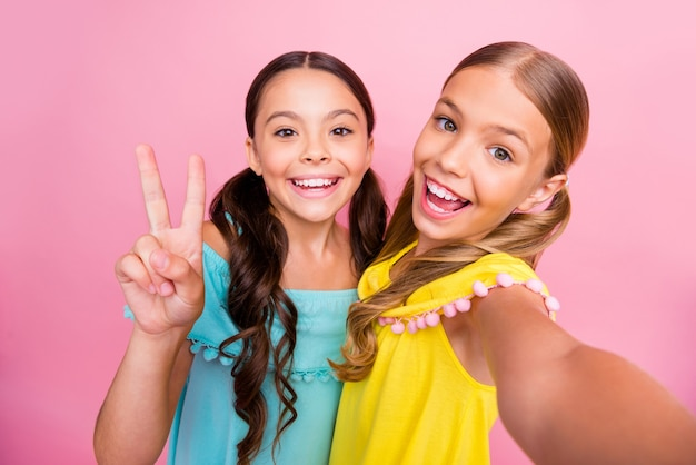 Маленькие девочки с косичками позируют на розовой стене