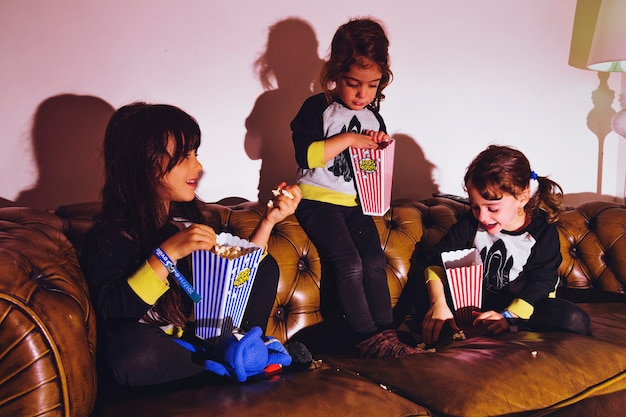 Little girls with popcorn on couch