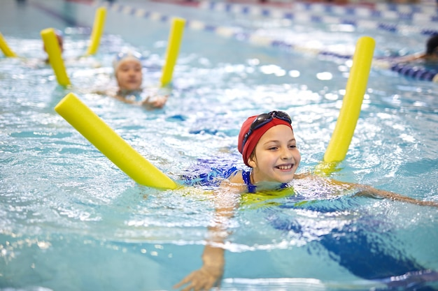 Little girls with swimming noodles in pool
