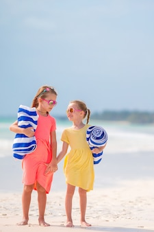 Little girls with towels ready for swimming at the sea on tropical beach