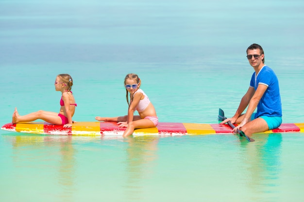 Little girls and young dad on surfboard during summer vacation