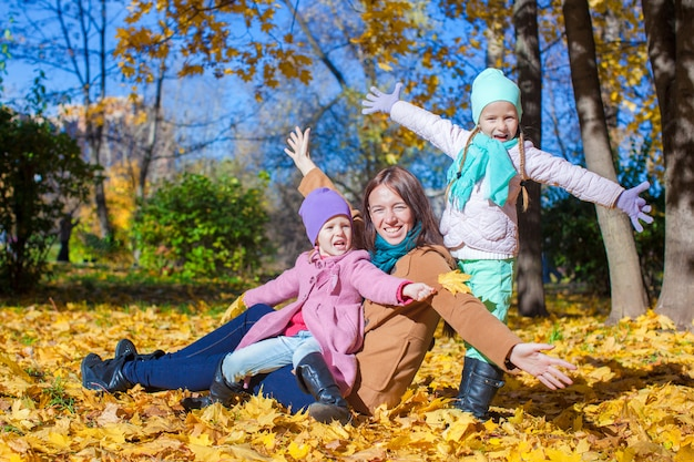 Little girls and young mother in autumn park have fun