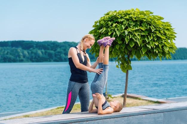 小さなガートと女性が湖のほとりの芝生で運動をしています。