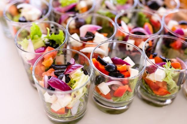 新鮮なサラダ、卵、サーモン、キュウリの白いテーブルの上に立っている小さなグラス