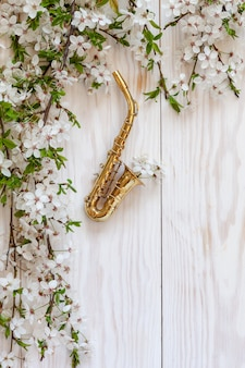 Little golden saxophone and blossoming cherry tree  branches.