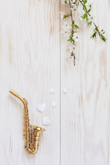 Little golden saxophone, white heart shape figurines  and blossoming cherry tree  branches.