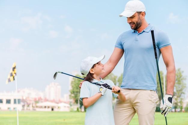 父と小さなゴルファー。幸せな青年と彼の息子はゴルフクラブを保持し、ゴルフコースに立っている間お互いを見ています