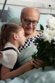 La nipotina abbraccia il nonno anziano che lo visita in corsia d'ospedale