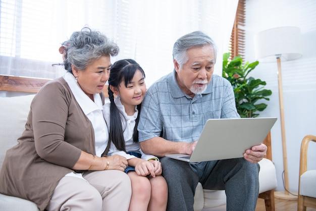 Little granddaughter teach senior elder to surf the internet using a laptop