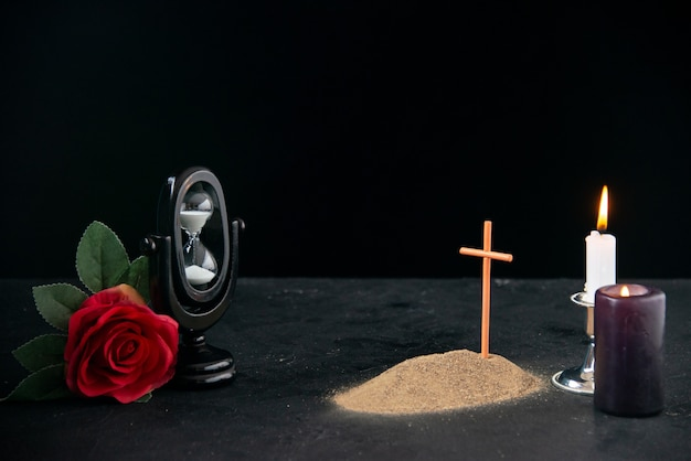 촛불과 꽃이 어두운 표면에 기억으로있는 작은 무덤