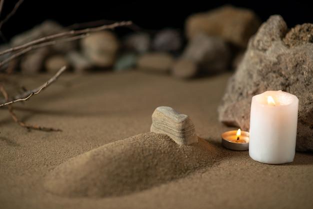 모래 장례식 죽음에 촛불과 돌이있는 작은 무덤