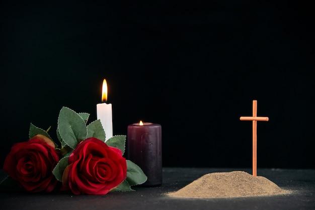 Piccola tomba con candela e fiori come memoria sulla superficie scura