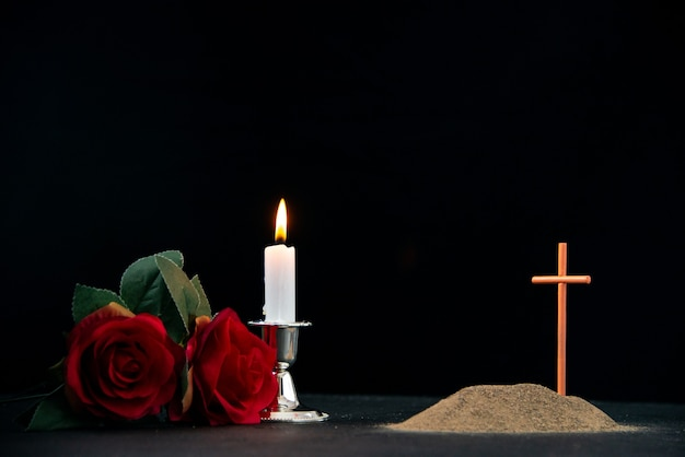 Little grave with candle and flowers as memory on dark surface