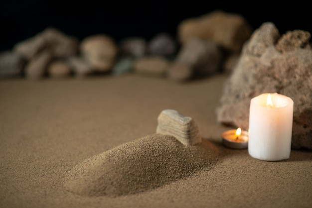 Little grave with candle and stones on sand funeral war death