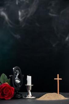 어두운 표면에 기억으로 붉은 꽃과 불없는 촛불이있는 작은 무덤