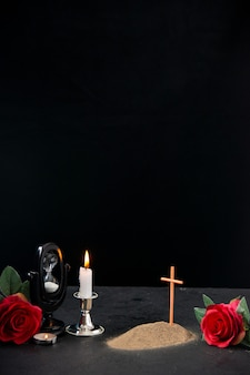 Little grave with red flower and burning candle as memory on dark surface