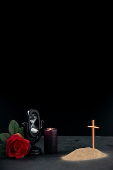 Little grave with red flower and hourglass as memory on a dark surface
