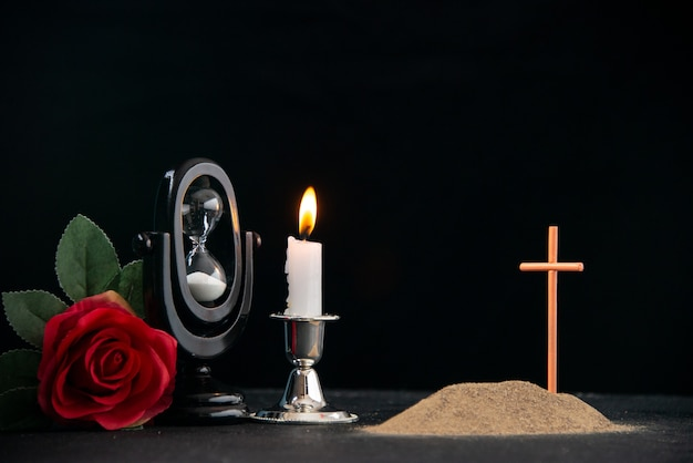 Little grave with red flower and hourglass as memory on the dark surface