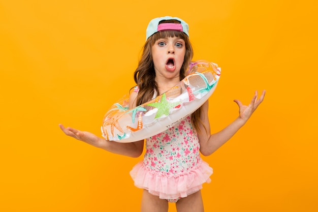 Little grimacing girl in a swimsuit with a swimming circle on an orange wall