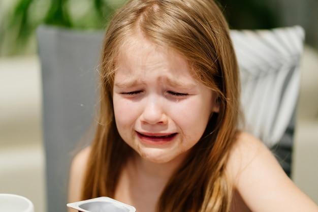 汚れた少女は夕食の席で泣きます。子供は食べることを拒否します。