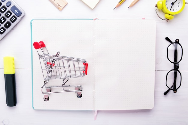 Little grocery trolley on notebook with stationery