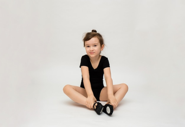 Little gymnast girl in a black uniform does a stretch on a white background