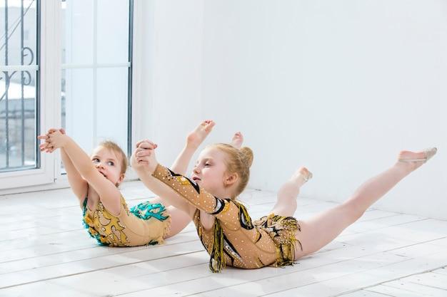 작은 체조 소녀 소녀와 댄서는 행복하고 귀여운 밝은 방에서 스트레칭을하고