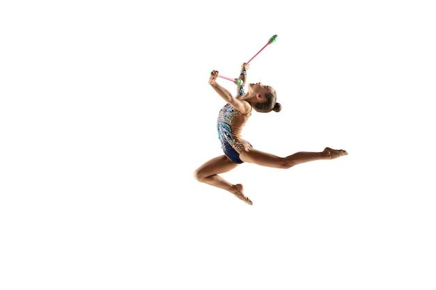 白いスタジオの壁に隔離された小さな体操の女の子。